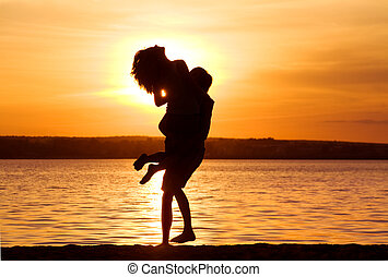 Silhouettes of happy guy holding his girlfriend by the lake at sunset
