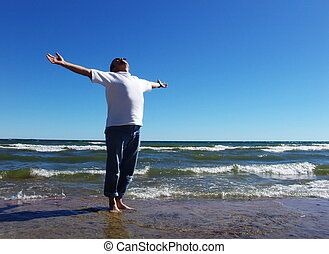 Joy - Man with arms outstretched standing on the lakeshore...