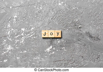 Joy word written on wood block. Joy text on cement table for your desing, concept