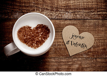 high angle view of a heart-shaped signboard with the text joyeuse st valentin, happy valentines day written in french, and a cup of cappuccino with a heart on its milk foam, on a wooden table