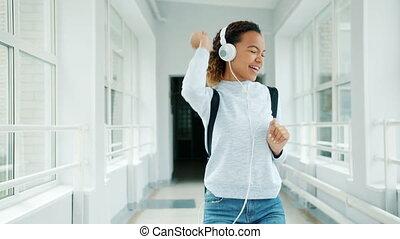 joyeux, amusement, girl, avoir, université, écouteurs, salle, chant, danse