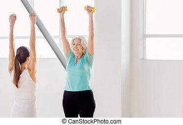 Joyful active woman lifting dumbbells
