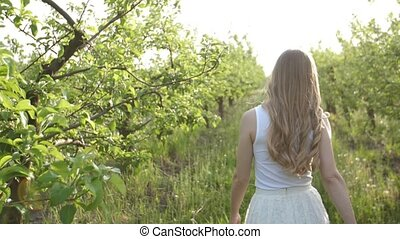 Joyful active woman walking through apple orchard - Rear...
