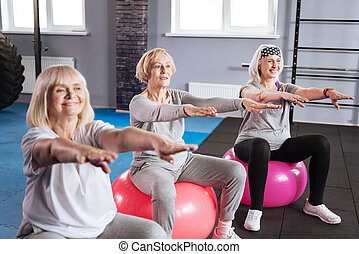 Joyful active women exercising on fitness balls