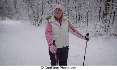 Joyful adult woman looking strangers. She stands in a snowy woods, around the trees grow tall. dressed in warm sportswear. In her hands stick for race walking.