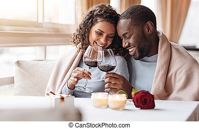 Joyful African American couple drinking wine in the restaurant
