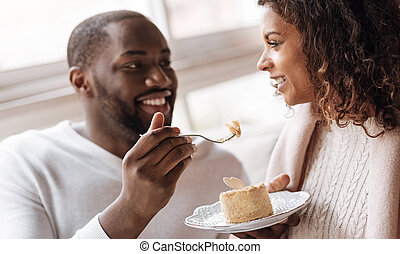 Joyful African American couple eating the dessert in the cafe