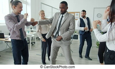 Joyful African American man is dancing among multi-ethnic group of colleagues having fun in workplace. Corporate parties and celebrations concept.
