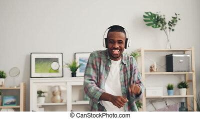 Joyful African American student is dancing singing and...