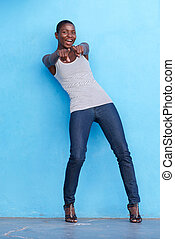 Joyful african woman standing and pointing