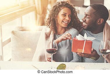 Joyful afro american man holding a present