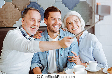 Joyful aged couple and their grandson resting in the cafe