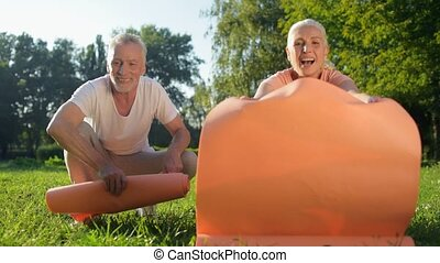 Joyful aged couple rolling out their exercise mats on the grass