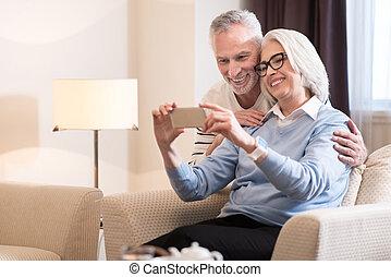 Joyful aged couple taking selfie at home