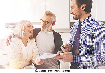 Joyful aged couple working with real estate agent