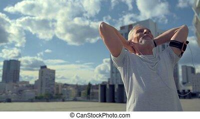 Joyful aged man enjoying sport in the city