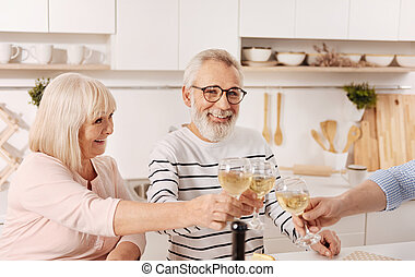 Joyful aged parents celebrating holiday with guests at home