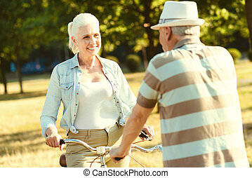 Joyful aged woman looking at her husband