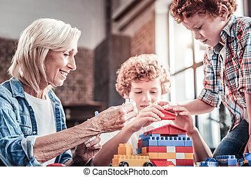 Joyful aged woman playing with her grandchildren