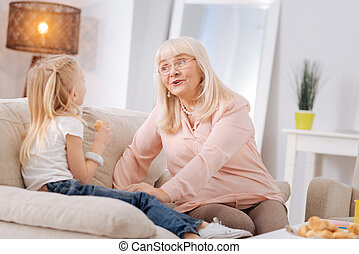 Joyful aged woman smiling to her granddaughter
