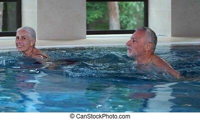 Joyful aging couple swimming in hotel pool indoors