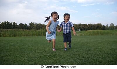 Joyful asian children running together in park