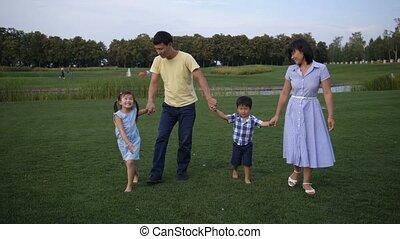 Joyful asian family walking holding hands in park