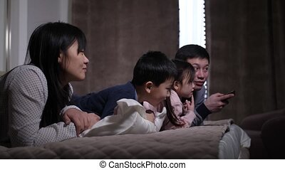 Joyful asian family with kids watching film on TV - Close-up...