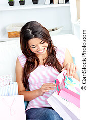 Joyful asian woman with shopping bags on the sofa