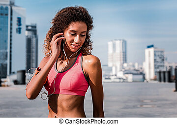 Joyful attractive woman listening to music during her workout