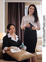 Joyful attractive women standing near the hotel maid - Hotel...