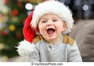 Joyful baby looking at camera in christmas at home