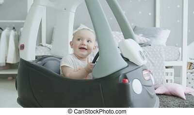 Joyful baby looking up sitting in toy car at home
