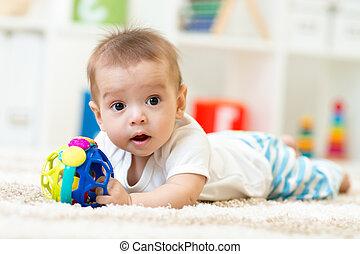 Joyful baby lying on the carpet in nursery room