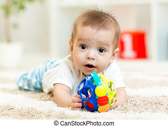 Joyful baby lying on the floor in nursery room