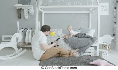 Joyful baby playing toys with beloved dad at home