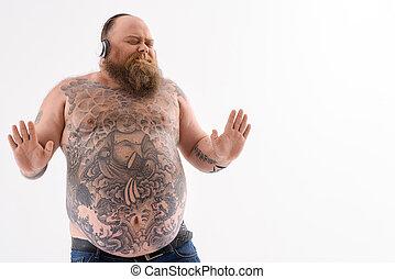 Joyful bearded fat guy listening to song