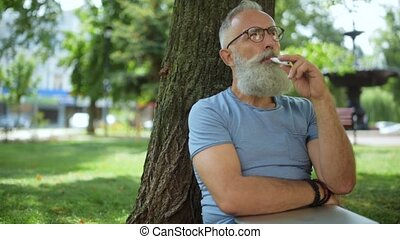 Joyful bearded vaper sitting under tree and smoking