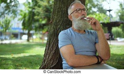 Joyful bearded vaper sitting under tree and smoking - Rest...