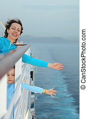 joyful beautiful woman with her daughter is standing on deck of cruise ship