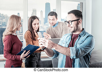 Joyful bespectacled man standing and using the smartphone.