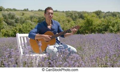 Joyful black guy playing guitar in lavender field