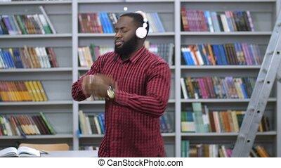 Joyful black man in headphones dancing in library - Joyful...