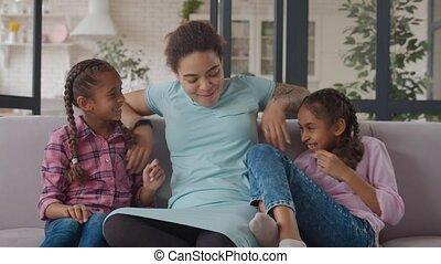 Joyful black mom and daughters having fun on couch - Joyful ...