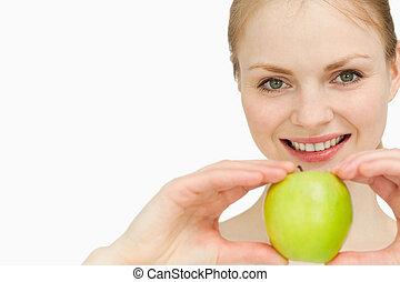 Joyful blond-haired woman presenting an apple