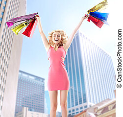Joyful blond woman jumping with paper bags