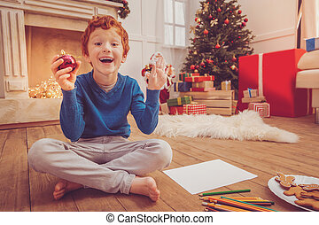 Joyful boy being excited about drawing Christmas decorations