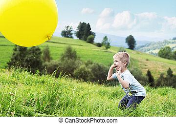 Joyful boy bouncing a balloon