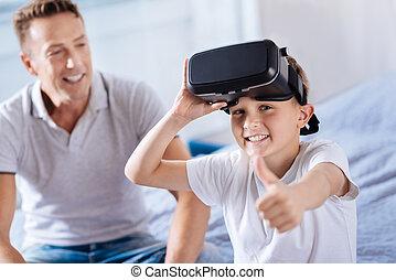 Joyful boy in VR headset showing thumbs up