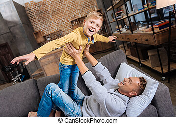Joyful boy playing with his father on sofa